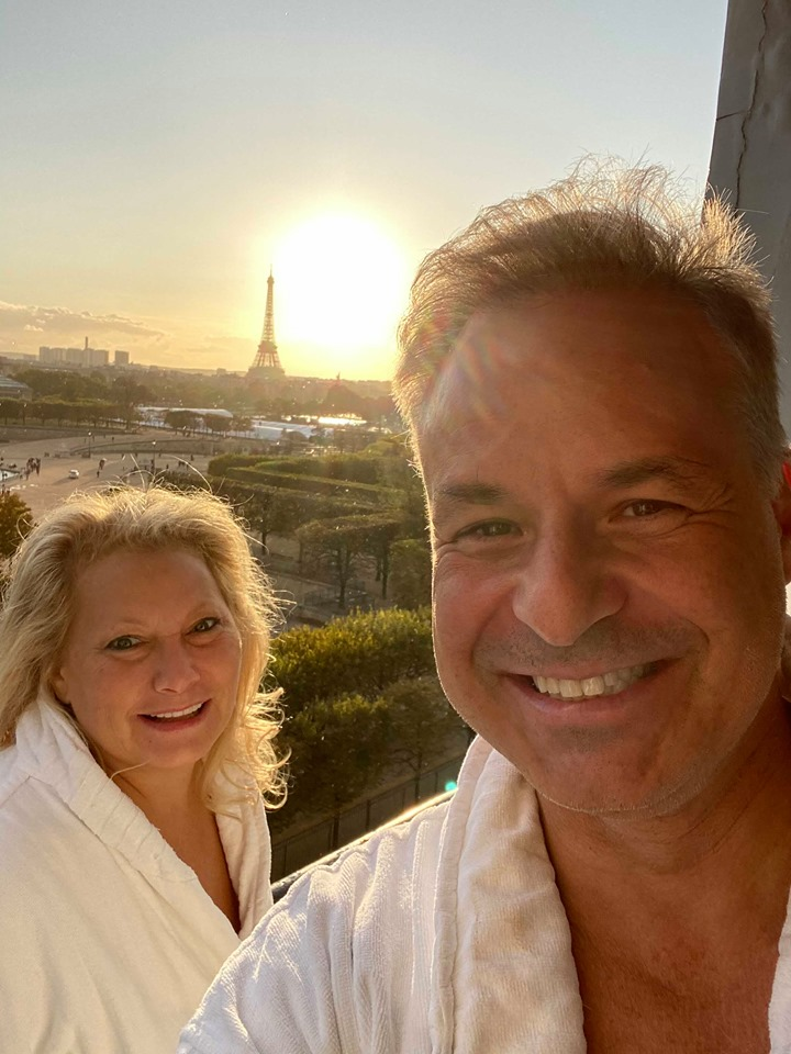 Clint Arthur and Alison Savitch wearing bathrobes, with the Paris sunset and the Eiffel Tower visible in the background