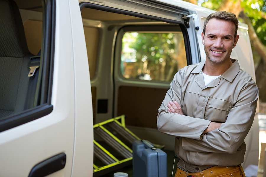 A man with his arms folded in front of his van for garage door repair in Seattle.