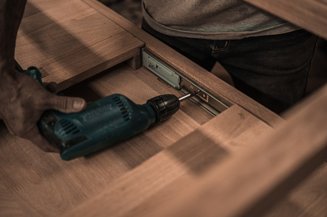 A man holding a drill to repair a garage door in Seattle.