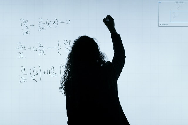 Woman standing at a board writing maths equations from her online tutor