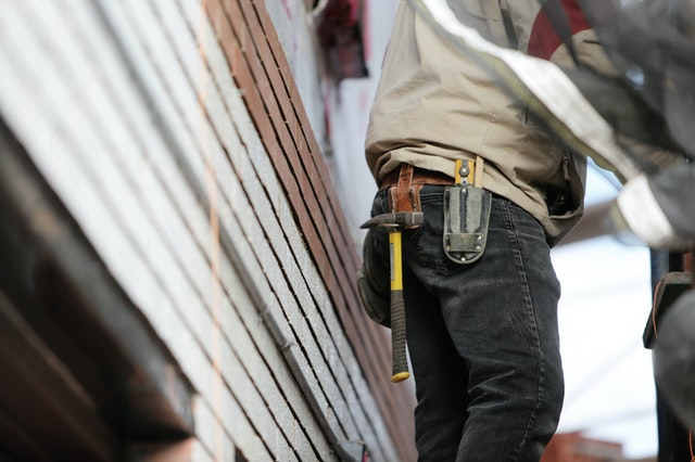 A man with a toolbelt repairing a garage door in Seattle.