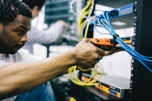 An electrician in Moncks Corner South Carolina using a screwdriver to do a services upgrade.