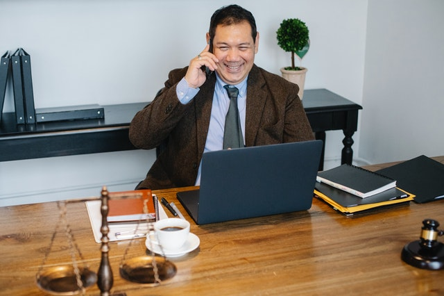 A malpractice lawyer smiling at his laptop in Hawaii.