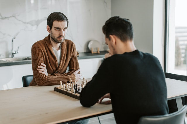 Two men sitting at a table playing chess on a chess set from a UK online store.