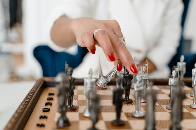 A woman moving chess pieces on a chess set she bought online in the UK.