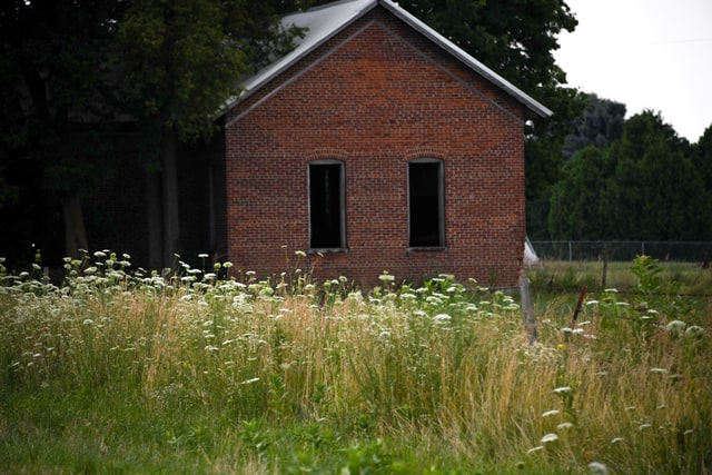 A custom-built amish building in a field.