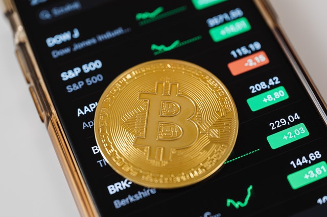 Bitcoin cryptocurrency on a phone with analysis website open.