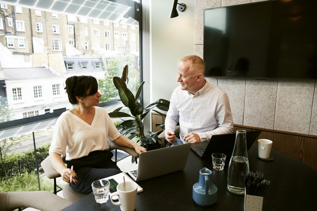 A man and a woman sitting using automation software for their business on their laptop.