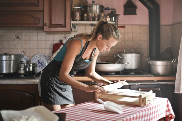 A woman cooking a recipe from a family-friendly blog. She is bent over with a rolling pin.