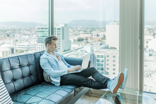 A man sitting on a couch with a laptop reading a website about the Internet of Things.