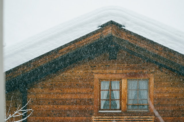 A custom built amish house in the snow.
