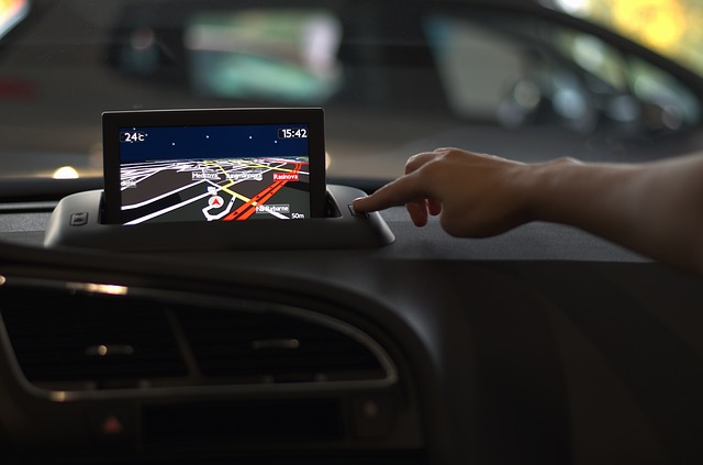 Someone pointing at a GPS product in a car.