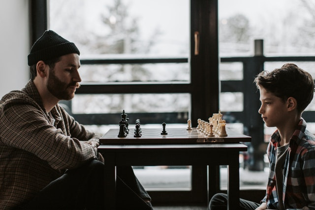 A father and son sitting opposite a chess set bough online in the UK.