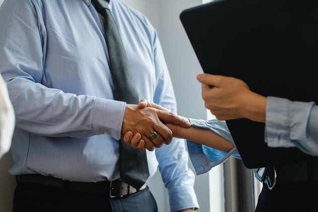 A credit repair company shaking hands with a client whose credit score they have fixed.
