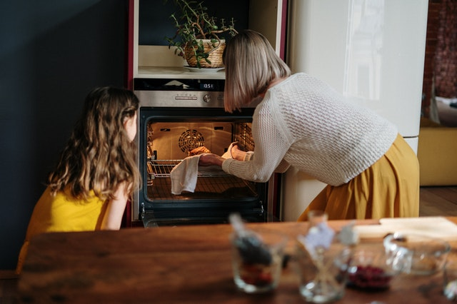 A woman and child putting something in the oven that they cooked from a family-friendly recipe blog.
