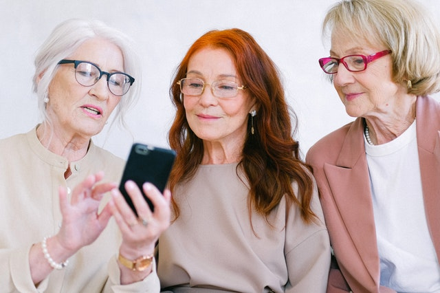 Three women smiling at a phone as they use it to SMS a business.