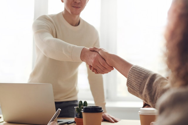 A credit repair company shaking hands with a client as they have fixed their credit score.
