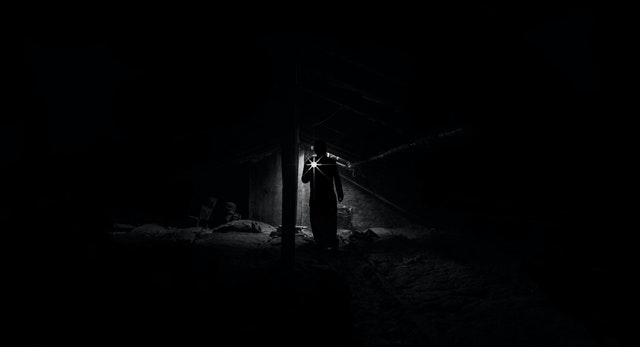 A man on a ghost tour America in the dark with a flashlight.