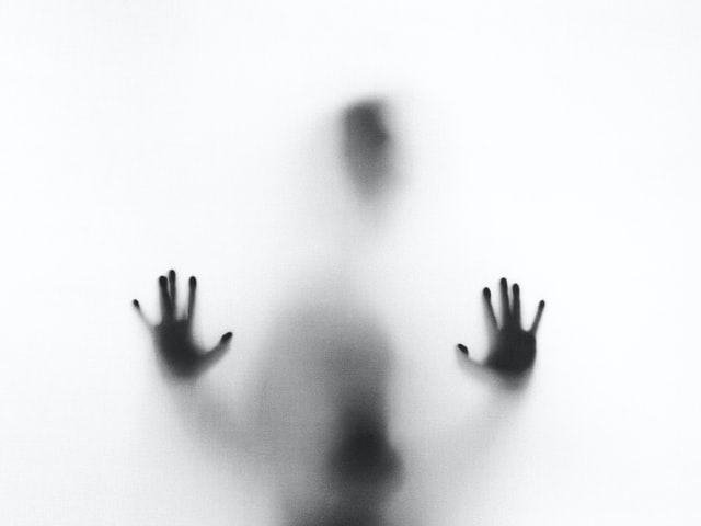 A ghost figure with its hands up in white smoke on a tour in America.
