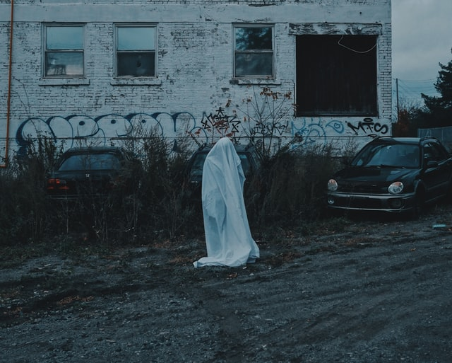 A ghost standing next to a building and a car on a ghost tour in America.