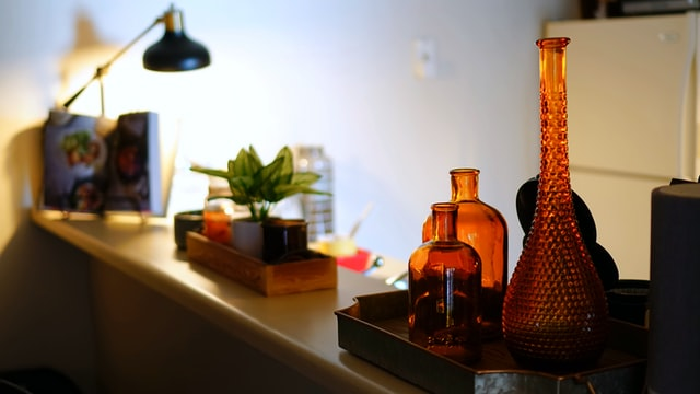 A counter with a lamp, plants and glass amber bottles that were bought from an online store.