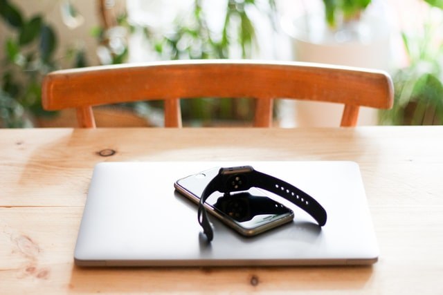 A laptop smartwatch and phone on a table as part of the Internet of Things.