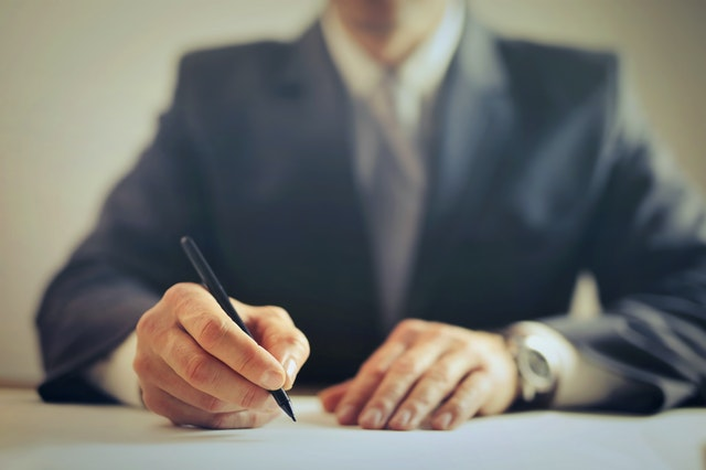 A malpractice lawyer in Hawaii writing notes on a piece of paper.