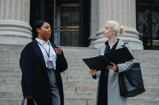 Two malpractice lawyers in Hawaii standing outside with an open folder talking.