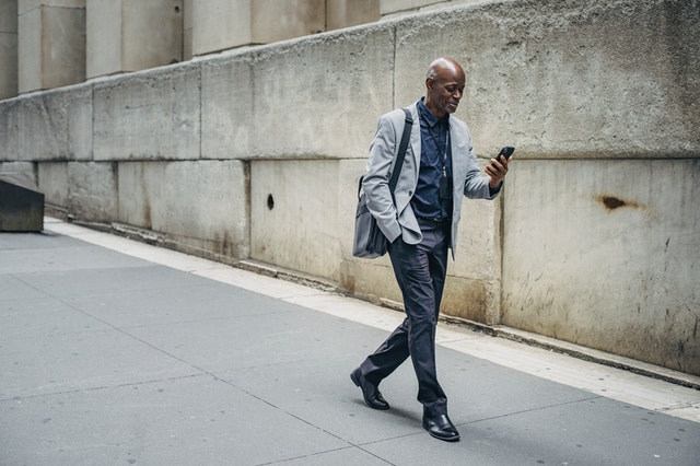 A man walking on the street looking at the business SMS he has received on his phone.