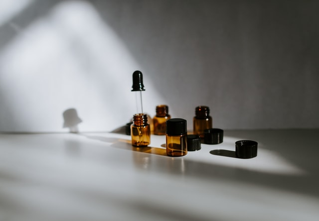 Small glass amber bottles with droppers for oil on a white table.