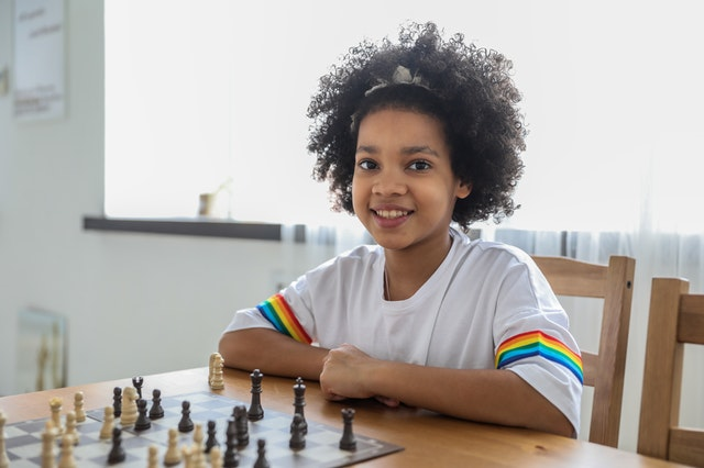 A girl smiling as she plays chess on a chess set bought online UK.