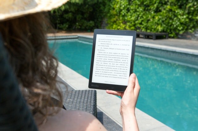 Woman by the pool wearing a hat reading an ebook.