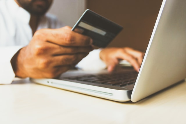 A man typing on a laptop and holding a credit card to get discounts at favorite online stores.