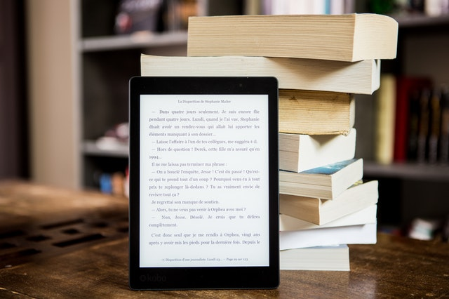 Ebook on a device propped up on a stack of books.