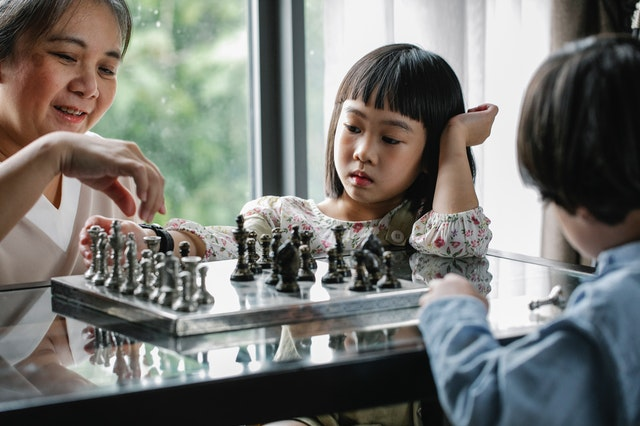 A group of kids playing on a chess set from an online store in the UK.