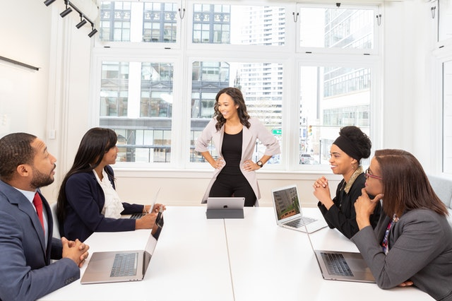 A team in a boardroom. One woman stands and discusses automation software for their business.