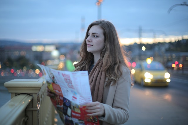 A woman on a bridge holding a map planning her travel itinerary.