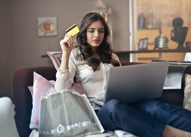 Woman with credit card looking at popup on a website.