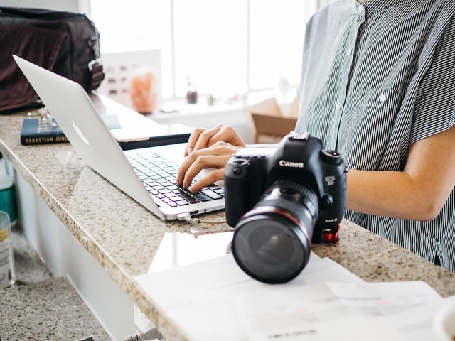 A photographer on a laptop with their camera next to them editing product photos in a 360 degree platform.