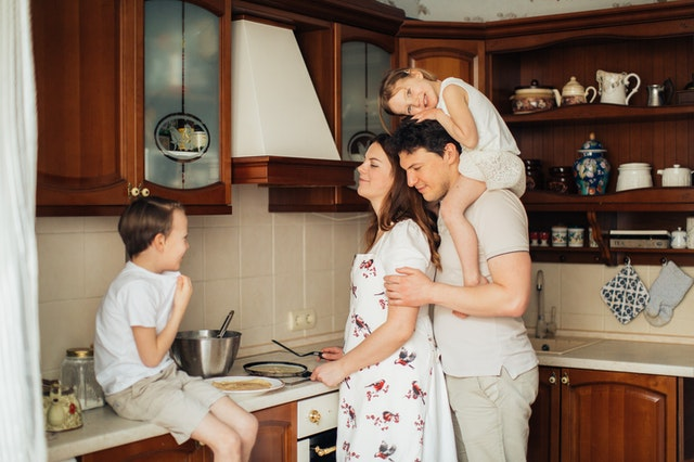 A family in a kitchen sitting on benches as they cook a recipe from a family-friendly blog.