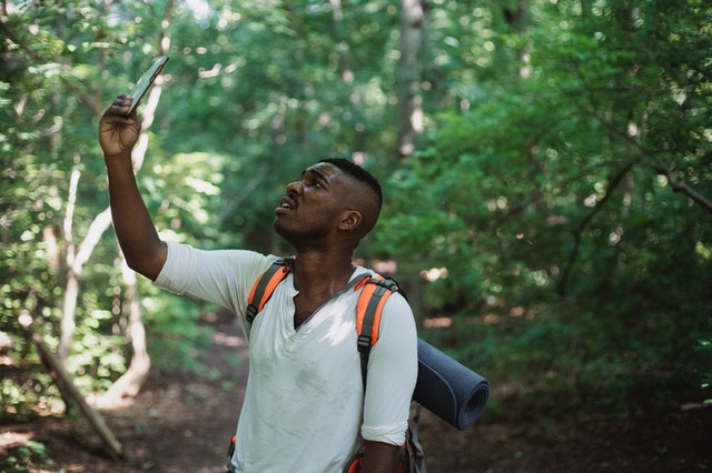 A man hiking holding up a GPS product from a store to navigate.