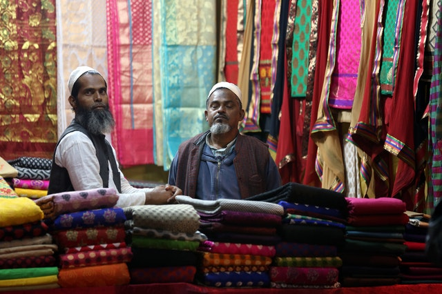 Two men working in a handmade textile shop with cloths around them.