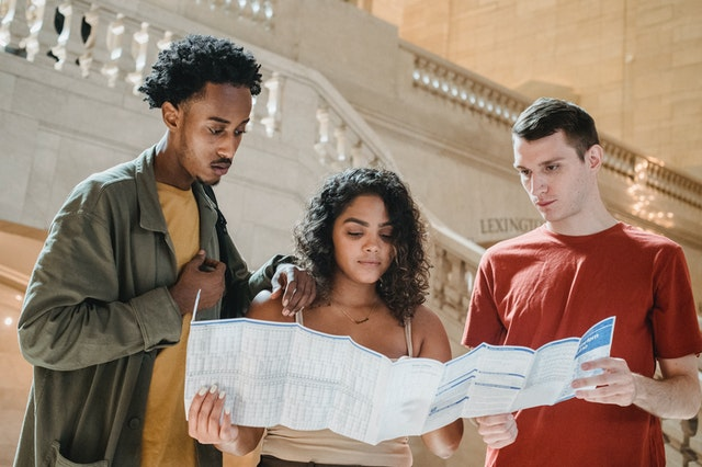 Three young people looking at a map planning their travel itinerary.