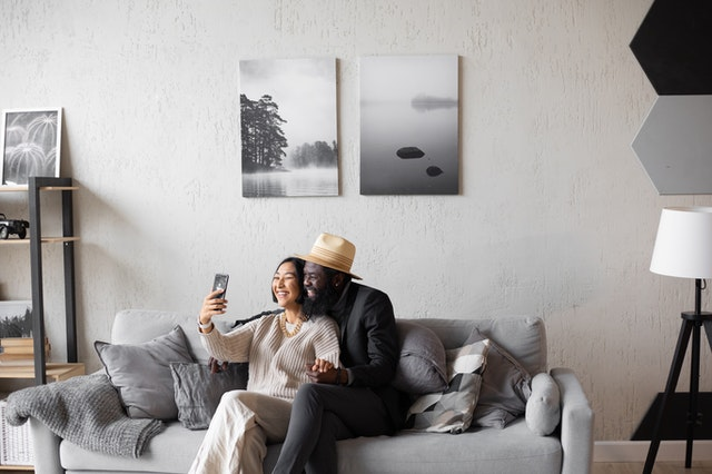 Two people sitting on a couch holding a phone up as they talk to someone on a random video chat app.