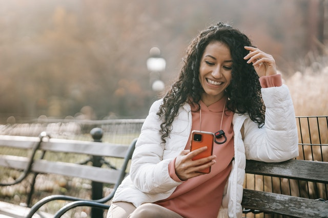 A woman sitting on a park bench smiling at her phone and the SMS texts she gets from a business app.