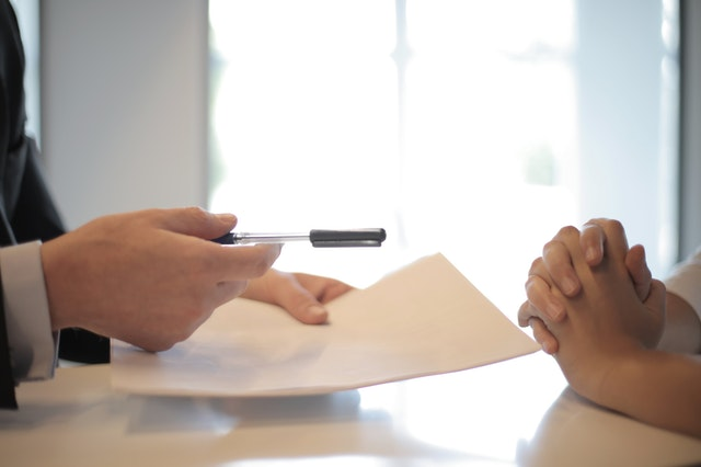 A California auto insurance company holding a piece of paper and pen and talking to a client.