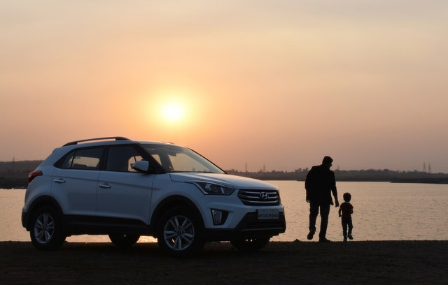 A man and his son at sunset with their car they are selling for cash on a USA website.