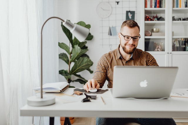 A man sitting at a desk smiling as he reads the casual mens lifestyle blog on his laptop.