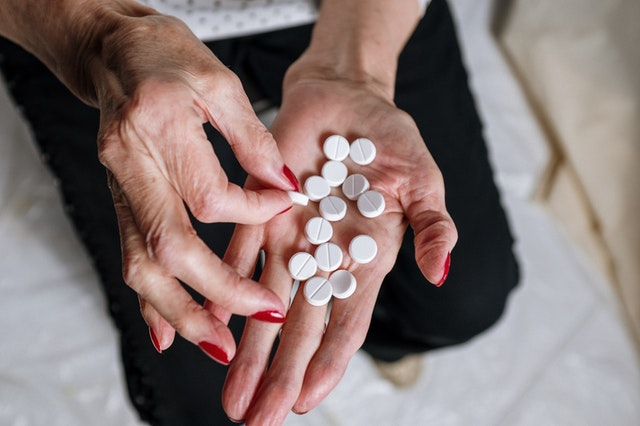 A woman holding pills from an online compounding pharmacy.