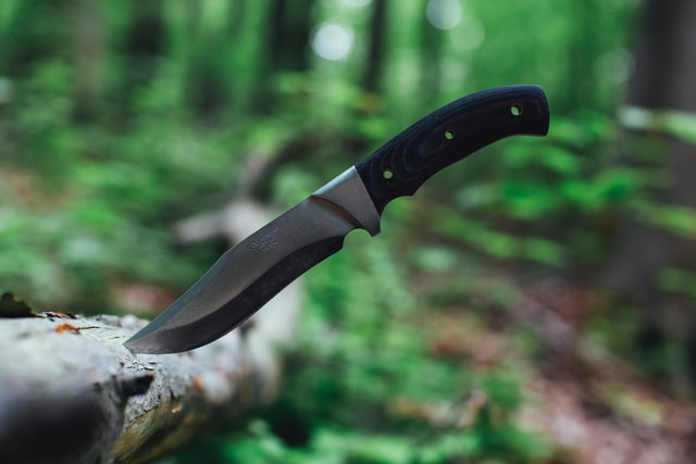 A French knife from an online store in a log outdoors.